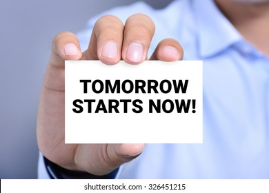 TOMORROW STARTS NOW! , message on the card shown by a man