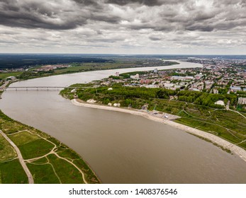 Tomsk cityscape and Tom river from aerial view. Modern city view. Dramatic landscape. Rainy and thunderstorm weather. Bridge through the river. Siberia, Russia