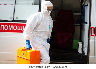 TOMSK, RUSSIA - APRIL 20, 2020: Doctor in personal protective equipment gets in an ambulance during coronavirus COVID-19 pandemic