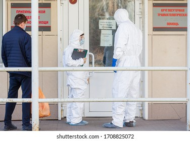 TOMSK, RUSSIA - April 20, 2020: Doctors in personal protective equipment stand with suspected coronavirus man near respiratory diseases hospital during the COVID-19 coronavirus pandemics