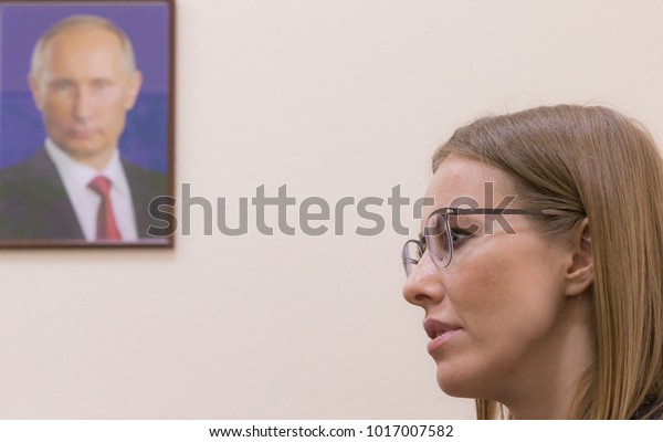 TOMSK, RUSSIA - JANUARY 19, 2018: Kseniya Sobchak russian TV presenter, journalist, socialite and actress on the background of Vladimir Putin portrait on the wall. Presidential candidate of the Russia