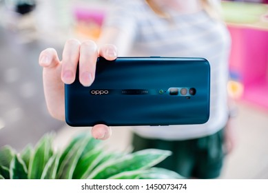 Tomsk, Russia - July, 07  2019: Ginger Woman holding Oppo Reno, oppo reno 10x zoom,  smartphone. Summer season horizontal view. Technology and communication concept. Oppo reno x10 zoom