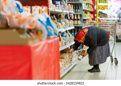 TOMSK, RUSSIA - June 19, 2019: Old woman consumer in supermarket. High prices and poverty problem