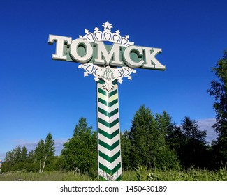 Tomsk, Russia - June 20, 2019: road monument-sign at the entrance to the Tomsk city against blue sky. Stylization under the Distance milepost of imperial Russia for road decoration. Translation: Tomsk