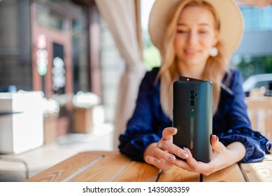 Tomsk, Russia - June 26 2019: Blonde Woman hands  holding Oppo Reno oppo reno 10x zoom smartphone. Summer season cafe horizontal view.