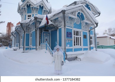 TOMSK, RUSSIAN FEDERATION - DECEMBER 30, 2016: Snow Maiden and blue wooden Russian-German house in Tomsk city (Russia). Girl in russian style with kokoshnik