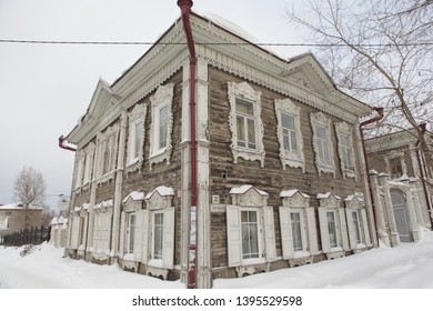 TOMSK, RUSSIAN FEDERATION - DECEMBER 30, 2016: Old wooden house with carved windows in Kartashov Street, 32, Tomsk city (Russia). Russian style in architecture and snowy winter