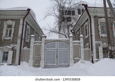 TOMSK, RUSSIAN FEDERATION - DECEMBER 30, 2016: Gate of old wooden house with carved windows in Kartashov Street, 32, Tomsk city (Russia). Russian style in architecture and snowy winter