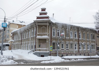 TOMSK, RUSSIAN FEDERATION - JANUARY 5, 2017: Old wooden house with carved windows and turret  in Lenin Avenue, 8, Tomsk city (Russia). Big icicles on roof - dangerous