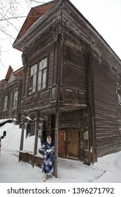 TOMSK, RUSSIAN FEDERATION - JANUARY 5, 2017: Old wooden house with carved windows and balcony in Voykov Street, 23, Tomsk city (Russia). Russian girl and russian style in architecture