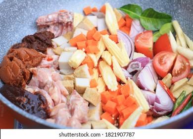 Tomyam paste, chilli in oil paste, chicken slice, fish cake, sliced onion, sliced tomato, chilli, diced carrot, sliced baby corn, kaffir lime leaves, lemongrass and galangal.