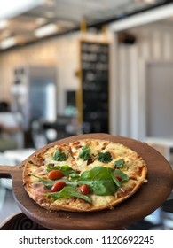 Tomyum koong pizza half with Rocket and Parma ham pizza on wooden pizza tray
