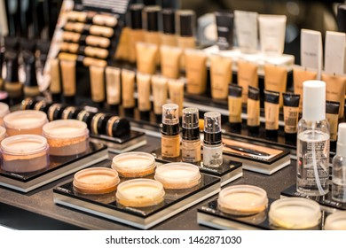 The tonal creams, powder, makeup base and correctors for the skin of the face in jars and tubes are set on the table in the shelves of a beauty salon. Shymkent, Kazakhstan July 8, 2019