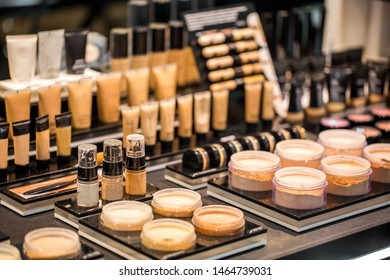 The tonal creams, powder, makeup base and correctors for the skin of the face in jars and tubes are set on the table in the shelves of a beauty salon. Probes different cosmetics.