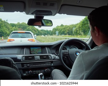 TONBRIDGE, ENGLAND, UK - JULY 01, 2017: A car interior and driver of a car stuck in traffic from roadworks on a motorway.