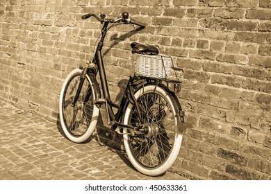 Toned. Black retro vintage bicycle with old brick wall and. Retro bicycle with basket in front of the old brick wall. Old photo effect applied.