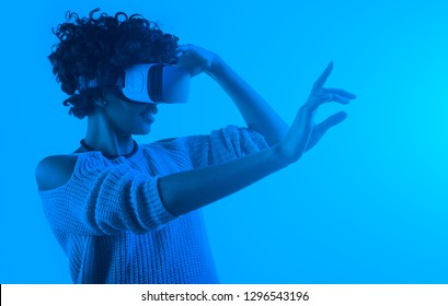 Toned in blue and monotone image of beautiful woman touching air during the VR experience