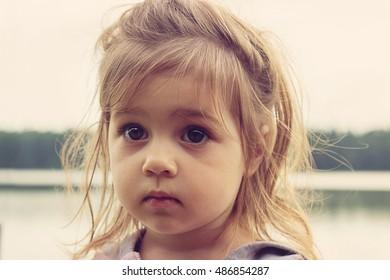 Toned closeup portrait of beautiful girl with big sad eyes