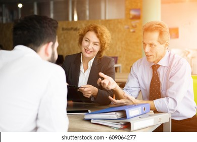 Toned of happy HR specialists smiling while taking interviews in office. Business representatives asking young man several questions connected with their company.