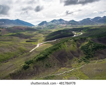 Toned image Aerial view of the volcanic mountain range and river at the cloudy sky background on the Kamchatka Peninsula in Russia
