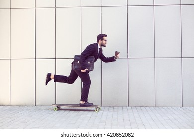 Toned image of businessman in black business suit on longboard walking with cup of coffee in his hand. Freelance man hurrying to his office.