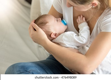 Toned image of cute baby boy sleeping on mothers hands
