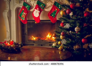 Toned image of empty wooden table in front of decorated fireplace and Christmas tree. Place for text. Suitable for Christmas background.
