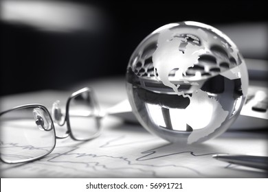 Toned image of glass globe with stock charts, calculator and spectacles