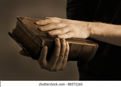 Toned image of a Man holding an old book in his hands.