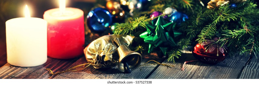 Toned image, purple. Christmas background, New Year, Christmas, gifts near a Christmas tree fluffy On a wooden table burning candles. Christmas decorations. Free space for text