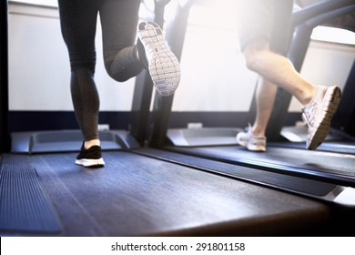 Toned Legs of Healthy Young Couple Exercising on Treadmill Device Inside Fitness Gym.