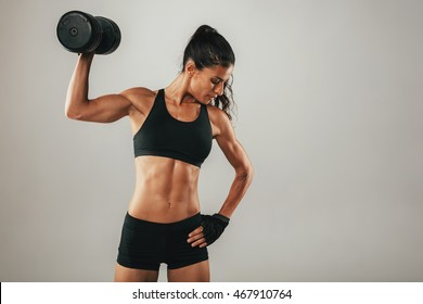 Toned muscular young woman working out with weights raising a dumbbell above her shoulder with a look of determination, three quarter on grey