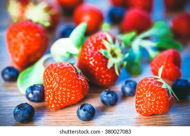 Toned photo. Color tone tuned. fresh raspberries, blueberries and strawberries on wooden background. Selective focus.