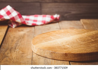 Toned photo. Color tone tuned. Wooden background with wooden table, tablecloth and round cutting board