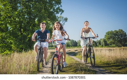 Toned photo of cute 10 years old girl riding bicycles with parents at field