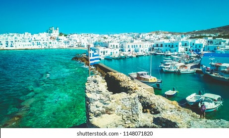 Toned photo of Greek national flag waving on the wind on the ruins of Venetian Castle with the view of a town of Naoussa as a background, Paros island, Greece