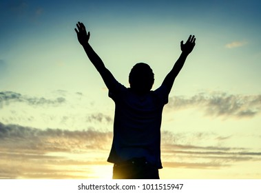 Toned Photo of Happy Man Silhouette with Hands Up on the Sky Background