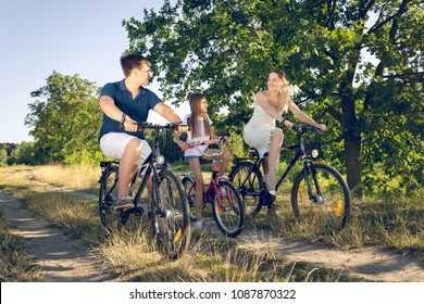 Toned photo of happy smiling family having fun and riding on bicycles in field