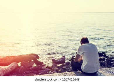 Toned Photo of Lonely Young Man at Seaside on Sunset Background