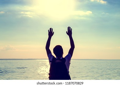 Toned Photo of a Man Silhouette with Hands Up on the Sea Background