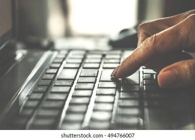 Toned photo. A man uses a laptop