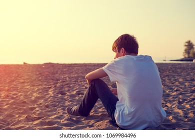 Toned Photo of Pensive Young Man sit on the Sand