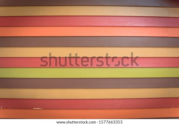 Toned photo rainbow color vinyl wooden siding panel background with imitation wood texture. House wood wall slice or planking vintage texture for horizontal background