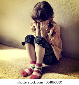 Toned Photo of Sad Little Girl on the Sofa in the Room