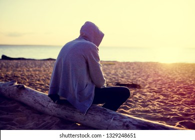 Toned Photo of Sad and Lonely Man in a Hoodie sit on the Log at Seaside