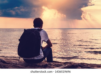 Toned Photo of Sad and Lonely Young Man sit at Seaside