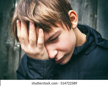 Toned Photo of Sad Teenager on the Wooden Wall Background
