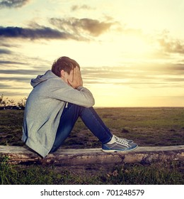 Toned Photo of Sad Teenager sit on the Sunset Background