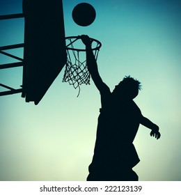 Toned Photo of Silhouette a Basketball Player on the Sky Background