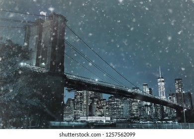 Toned photo of skyscrapers of Manhattan and Brooklyn bridge at snowy winter night. Famous bridge. Postcard view of New York.